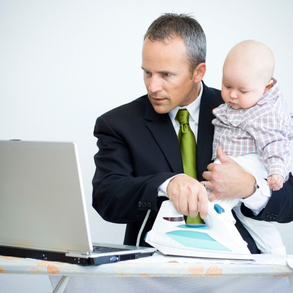 Man wfh with baby and ironing